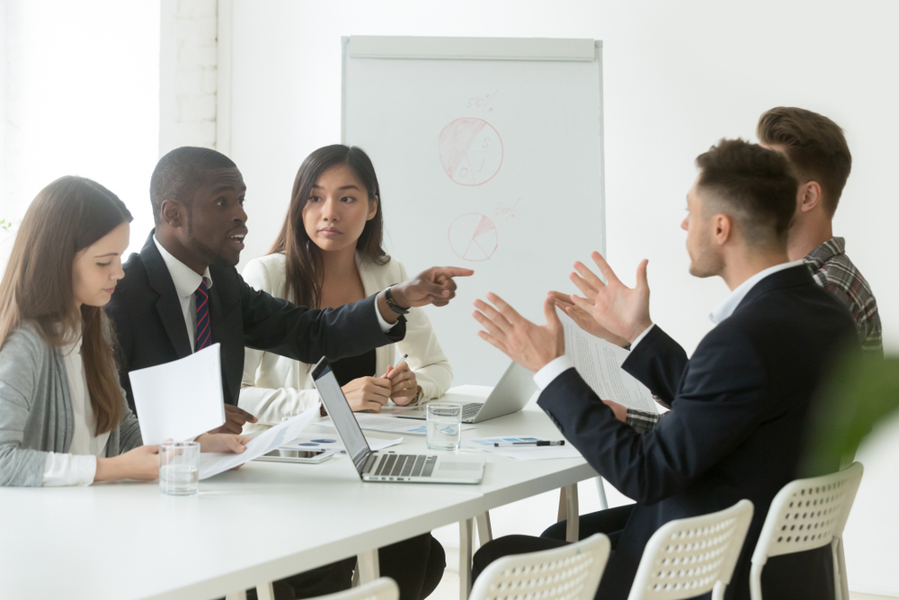 team sitting at table in conference room having a conversation